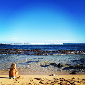 Girl sitting on the beach at hookipa